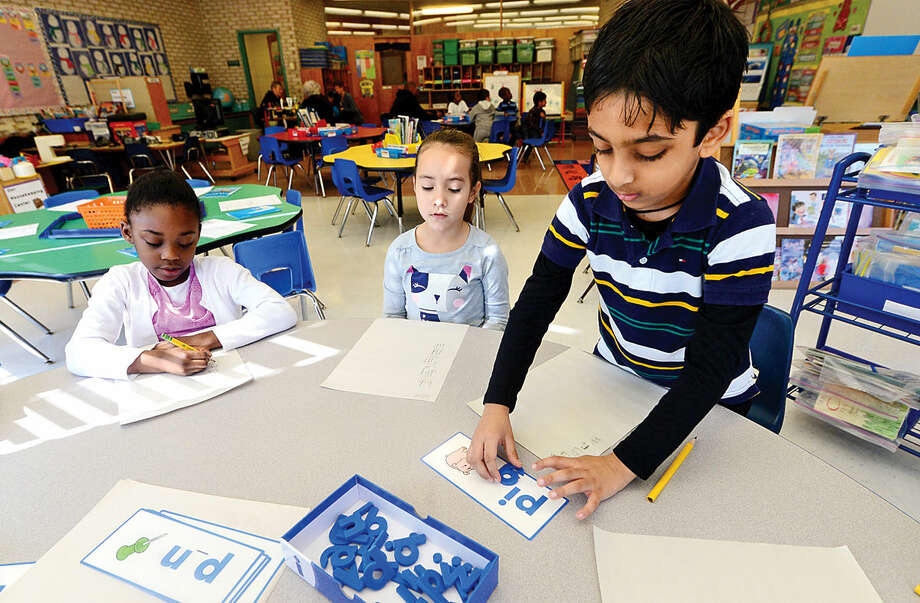 Hour photo / Erik Trautmann Fox Run Elementary School kindergartners Alexandra Coddett, Emily Marcelino and Ayan Patel get introduced to the CK3LI reading program as part of a test run for the program Friday.