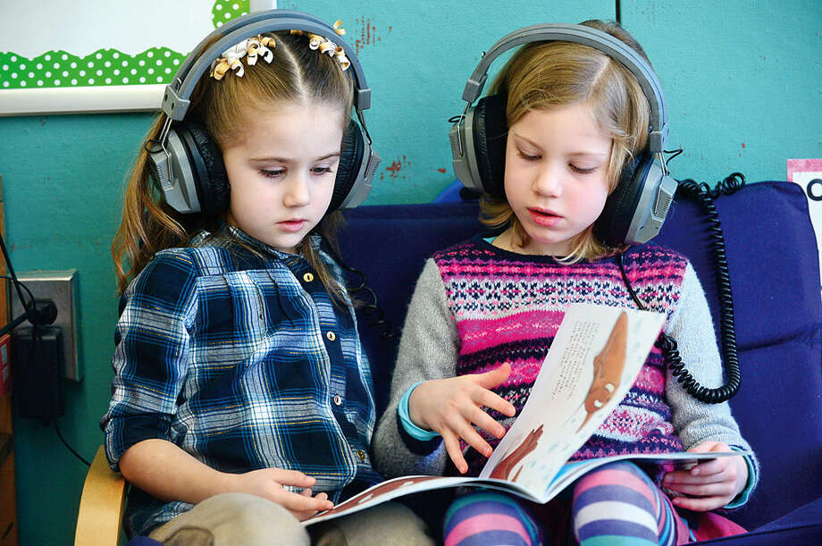 Hour photo / Erik Trautmann Fox Run Elementary School kindergartners Charlotte Hamilton and Anna Spence get introduced to the CK3LI reading program as part of a test run for the program Friday.