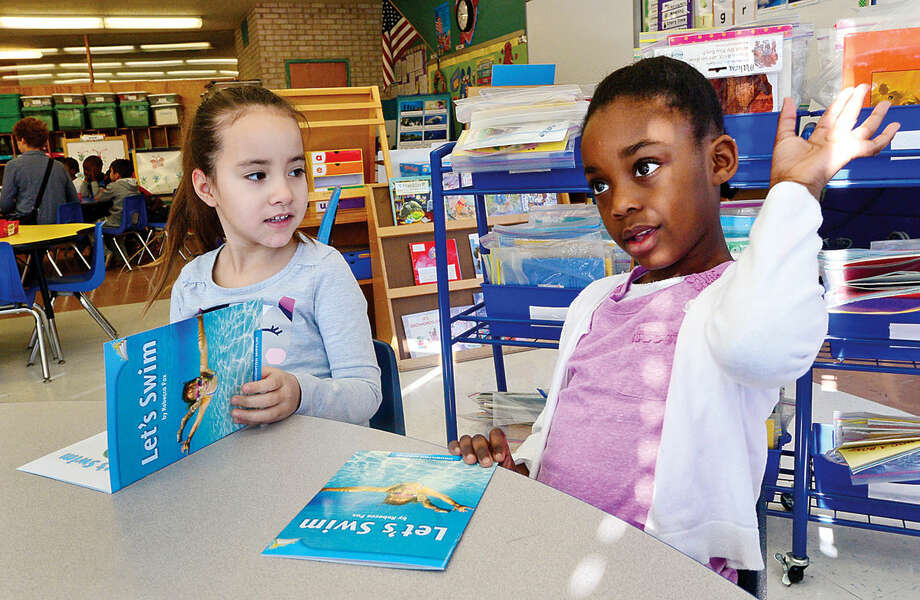 Hour photo / Erik Trautmann Fox Run Elementary School kindergartners mily Marcelino and Alexandra Coddett get introduced to the CK3LI reading program as part of a test run for the program Friday.