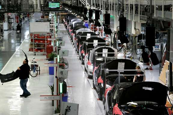 A worker carries a front end part along the assembly at Tesla Motors, California's only full-scale auto manufacturing plant, as seen on Thurs. Feb. 19, 2015,  in Fremont, Calif.