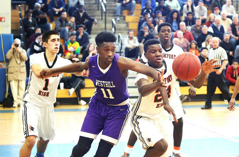 Westhill's #11, Lenold Auguste, trys to get the ball from Stamford's #24, Nii Pobee, during an FCIAC playoff game at Fairfield Ludlowe High School Saturday afternoon.