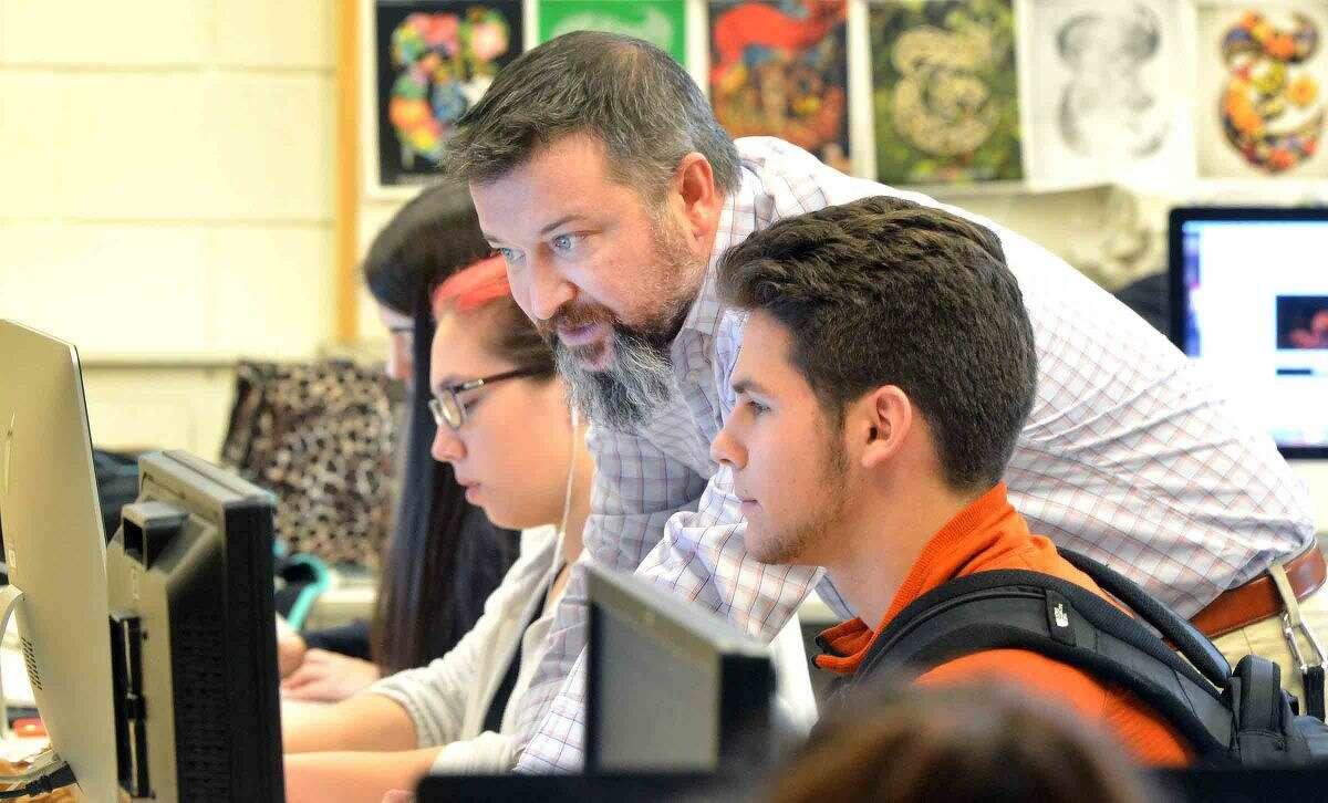 Hour Photo/Alex von Kleydorff Norwalk High School Jr. Reid Singewald talks with teacher Robert Karl about his article on health concerns with cell phones during Journalism class
