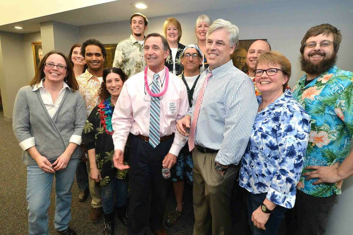 Hour Photo/Alex von Kleydorff During a party at City Hall on his last day on the job after 37 years, Micheal B Greene gets in a group photo with Acting Director of Planning and Zoning Michael E. Wrinn, joined by City Hall employees in Hawaiian shirts to wish him well