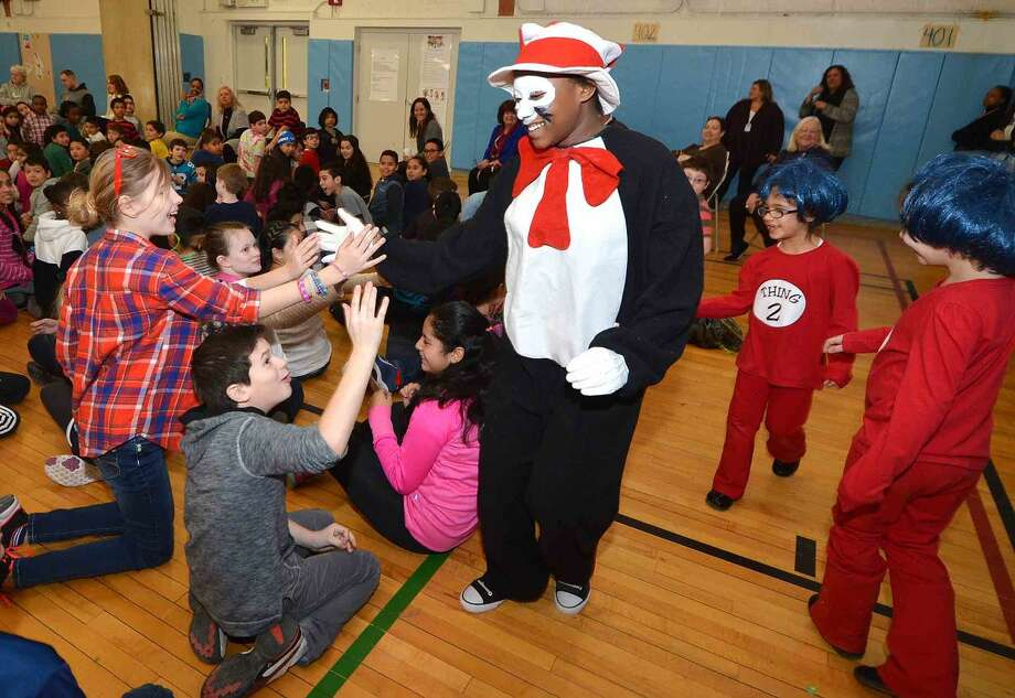 Hour Photo/Alex von Kleydorff High Fives from 5th grader Trinity Oliver as the Cat in the Hat followed by Camila Pajares as Thing 1 and Jaqueline Gama as Thing 2 to kick off Read Across America day at Brookside School on Friday