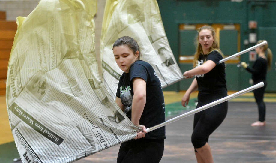 Hour Photo/Alex von Kleydorff. Lucie Sullivan rehearses with others in the Color Guard flag line for this weekends Winterguard and Percussion Show