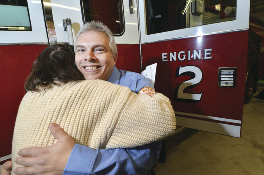 Hour Photo/Alex von KleydorffWilton Firefighter Tom Coon gets a hug from Fire Department Administrator Kathy Horn as she wishes him well on his retirement after 33 years of service with the department.