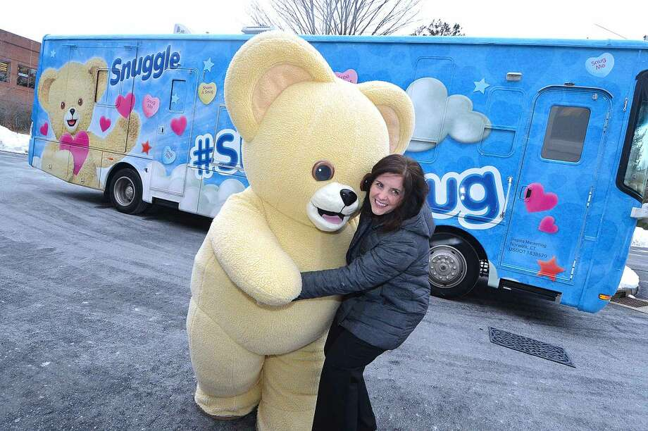 Hour Photo/Alex von Kleydorff Sara Mayer, Associate Brans Manager gets a hug from Snuggle as she sees the snug bus for the first time