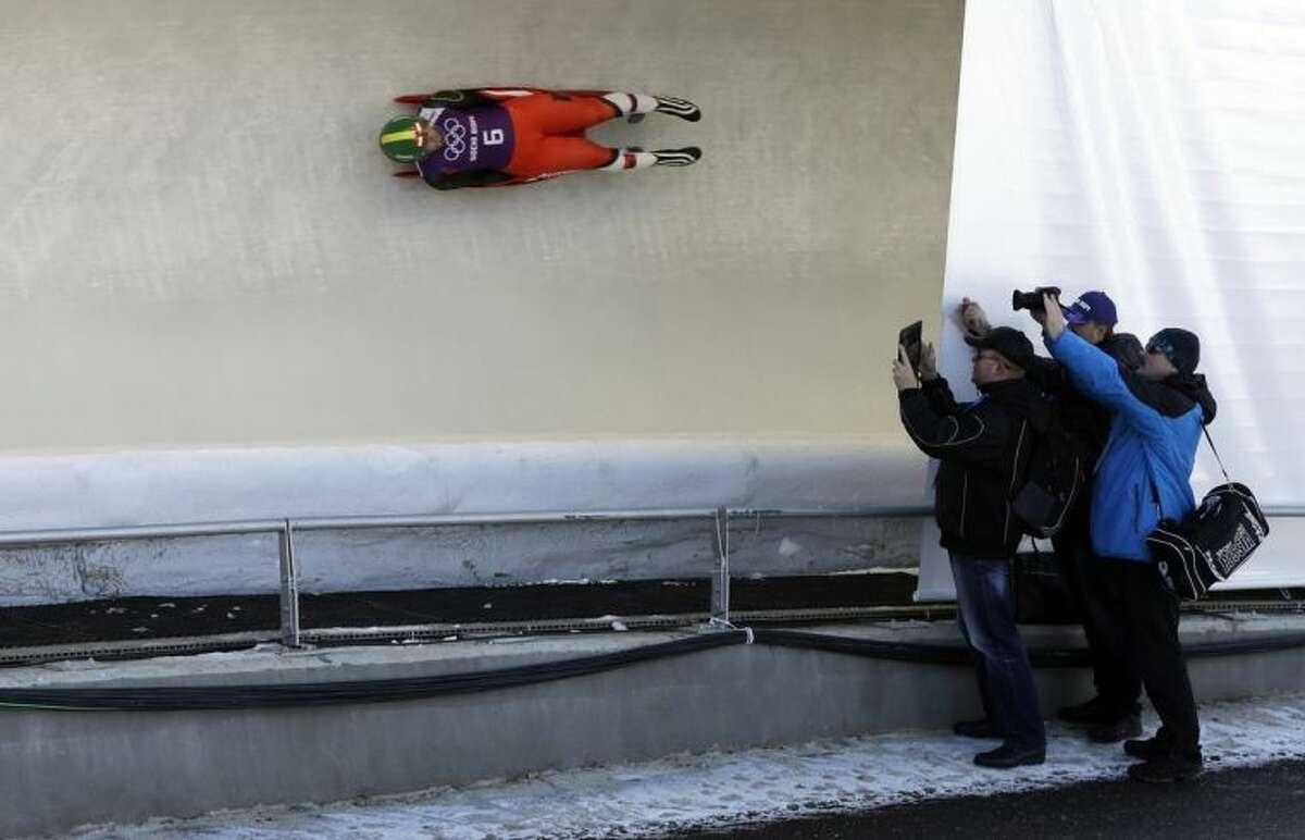 Members of the Russian team photograph Nina Reithmayer of Austria during a training run at the 2014 Winter Olympics, Tuesday, Feb. 4, 2014, in Krasnaya Polyana, Russia. (AP Photo/Natacha Pisarenko)