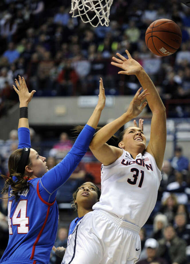 Connecticut's Stefanie Dolson (31) drives past SMU's Mallory Singleton (44) during the first half of an NCAA college basketball game in Storrs, Conn., Tuesday, Feb. 4, 2014. (AP Photo/Fred Beckham)
