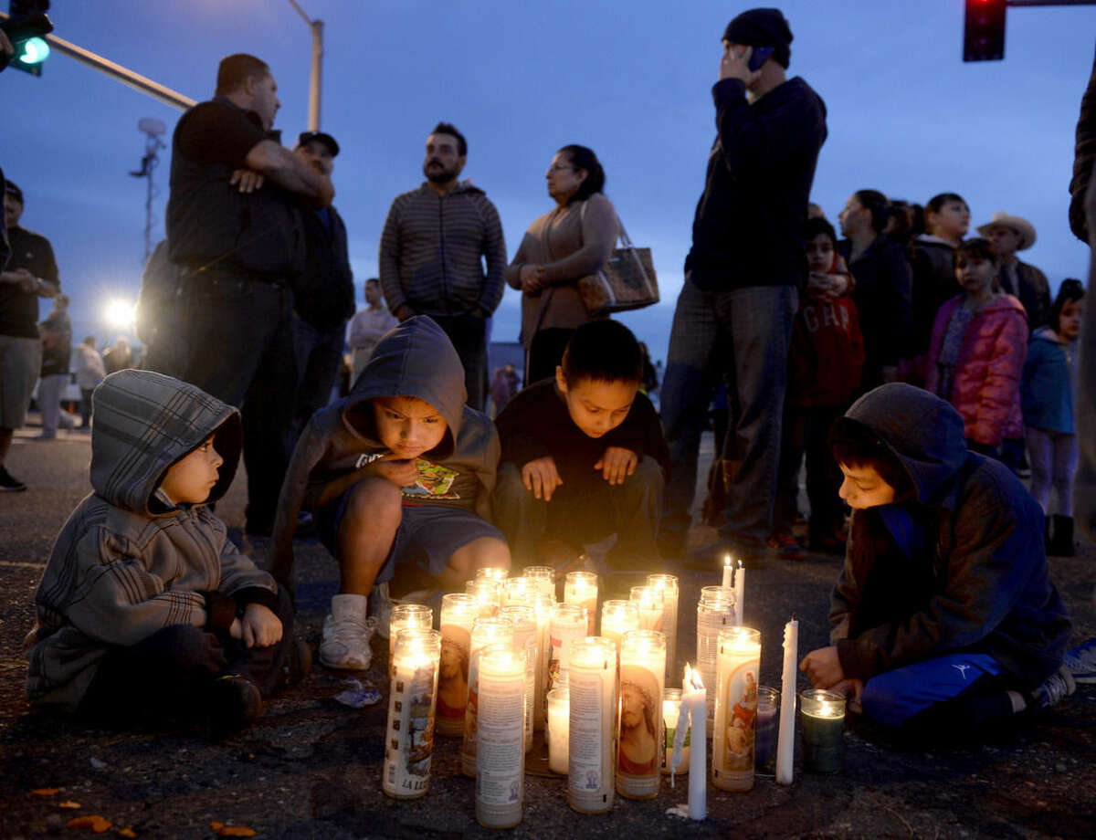 Pasco, Wash., residents, from left foreground to right, Angel Morgan, 5, and his brother Jose Morgan, 6, as well as Alex Gonzalez, 4, and his brother Angel Gonzalez, 8, gather around a candlelit vigil Wednesday, Feb. 11, 2015, in memory of Antonio Zambrano-Montes who was fatally shot by police after a confrontation on Tuesday. (AP Photo/The Tri-City Herald, Sarah Gordon) LOCAL TELEVISION OUT; LOCAL RADIO OUT KONA