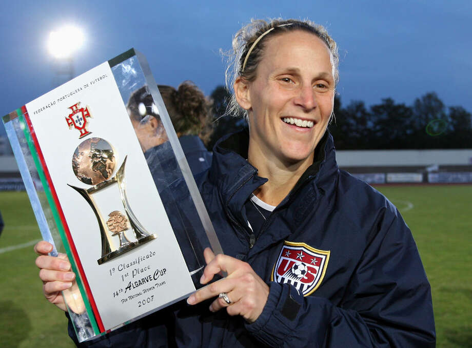 FILE - In this March 14, 2007, file photo Kristine Lilly, team captain of the United States, holds the winner's trophy after they defeated Denmark 2-0 in the women's soccer Algarve Cup final in Vila Real de Santo Antonio, Portugal. A day after her former team faces England in an exhibition, Lilly will be inducted into the National Soccer Hall of Fame. (AP Photo/Steven Governo, File)