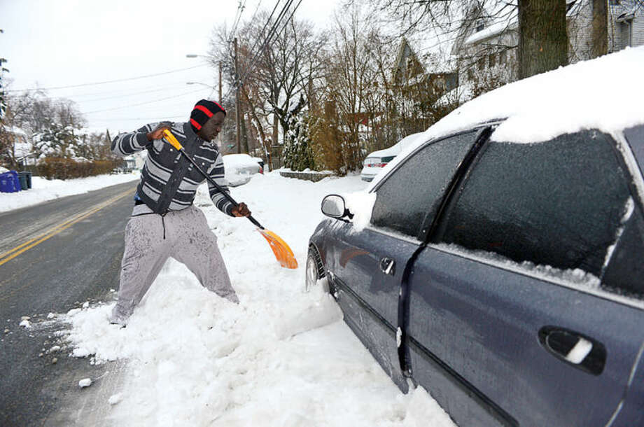 Hour photo / Erik Trautmann Chilly Sye digs out his vehicle following the recent snowfall that left 5 inches of wet snow for commuters to deal with Wednesday morning.