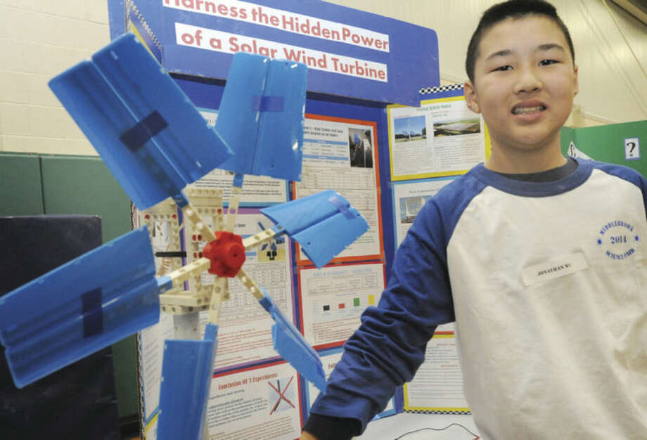 "Hour photo / Matthew VinciSeventh-grader Jonathan Wu stands next to his project, ""Harness the Hidden Power of a Solar Wind Turbine"" at the Middlebrook School Science Fair in Wilton on Tuesday."