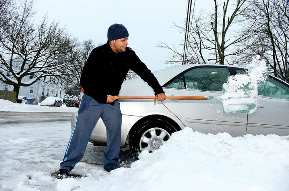 Hour photo / Erik Trautmann Eddie Perdomo digs out his vehicle of Strawberry Hill Ave following the recent storm that left 5 inches of wet snow for commuters to deal with Wednesday morning.