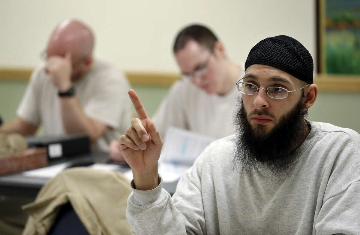 In this photo taken Thursday, Jan. 28, 2016, inmate Jayson Bush raises his hand in a college world history class at the Monroe Correctional Complex in Monroe, Wash. College education in American prisons is starting to grow again, more than two decades since federal government dollars were prohibited from being used for college programs behind bars. The shift comes as everyone from President Barack Obama to state policymakers are looking for ways to get better results from the $80 billion the U.S. spends annually on incarceration. (AP Photo/Elaine Thompson)