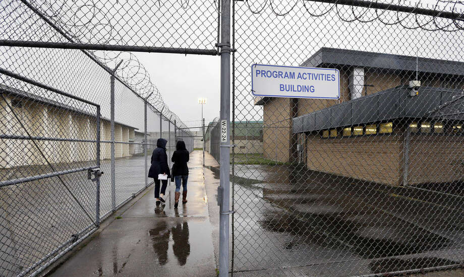 In this photo taken Thursday, Jan. 28, 2016, staff members head past razor wire-topped fences and into a building hosting a University Behind Bars program at the Monroe Correctional Complex in Monroe, Wash. College education in American prisons is starting to grow again, more than two decades since federal government dollars were prohibited from being used for college programs behind bars. The shift comes as everyone from President Barack Obama to state policymakers are looking for ways to get better results from the $80 billion the U.S. spends annually on incarceration. (AP Photo/Elaine Thompson)