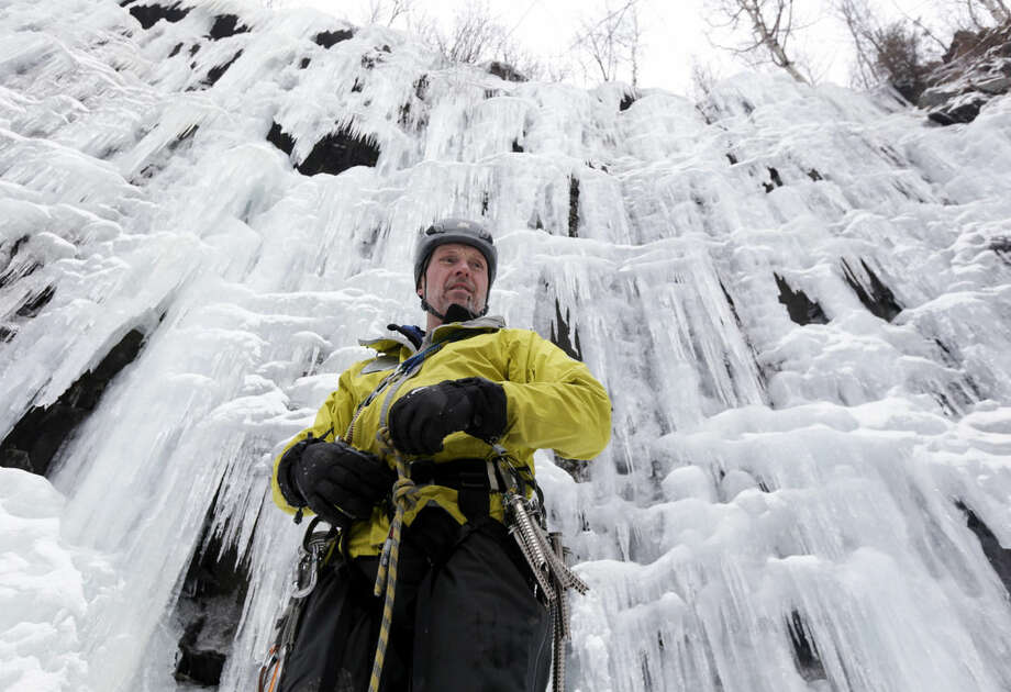 In this Wednesday, Feb. 10, 2016 photo, ice climber Don Mellor prepares to climb Pitchoff Quarry in Keene, N.Y. Mellor began ice climbing in the make-your-own tools era and has since introduced the sport to generations of students at a Lake Placid prep school where he is a teacher and counselor. He wrote the book, literally, on ice climbing in this rugged region. (AP Photo/Mike Groll)