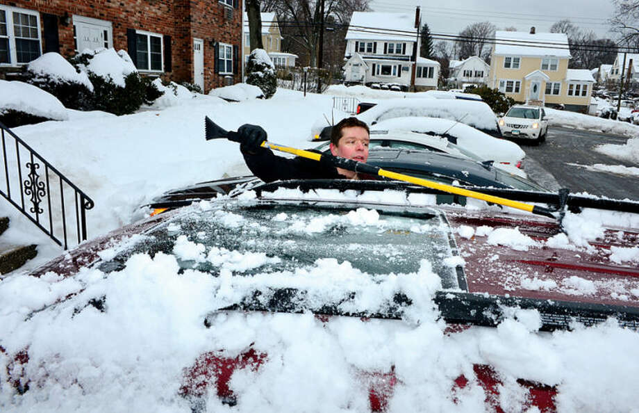 Hour photo / Erik Trautmann Sebastian Serre clears of his car following the recent winter storm that left 5 inches of wet snow in Stamford Wednesday morning.