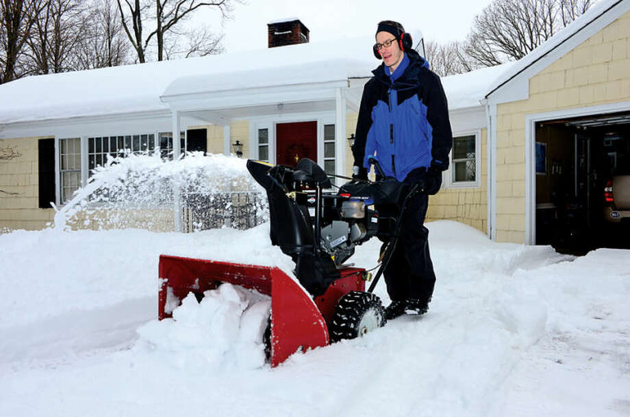 Hour photo / Erik Trautmann Drek Moe clears snow from his driveway in Wilton following the recent winter storm that left 5 inches of wet snow Wednesday morning.