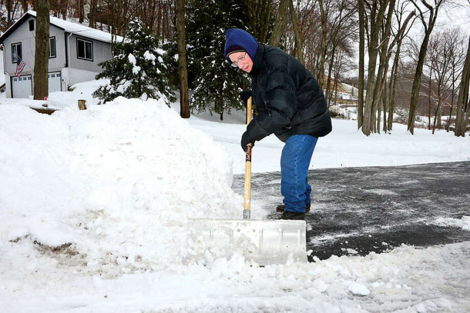Hour photo / Erik Trautmann Frank Dunn clears snow from his driveway on Horseshoe Rd in Wilton following the recent winter storm that left 5 inches of wet snow Wednesday morning.