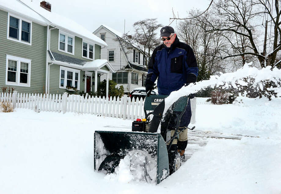 Hour photo / Erik Trautmann Pat Boyle throws snow off the walk in front of his residence on Field st in Stamford following the recent winter storm that left 5 inches of wet snow Wednesday morning.