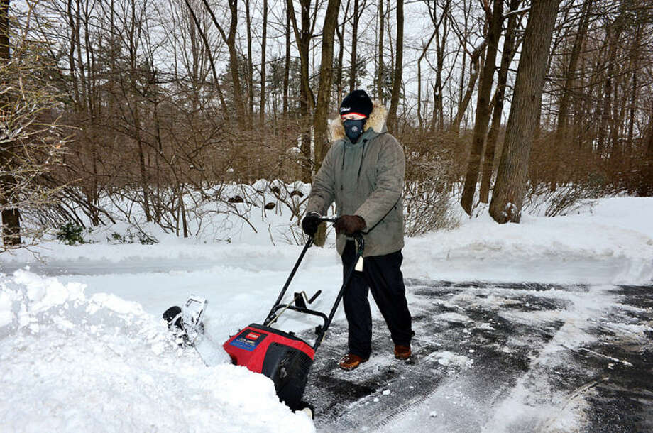 Hour photo / Erik Trautmann Len Pelletiere clears snow from his driveway in Wilton following the recent winter storm that left 5 inches of wet snow Wednesday morning.