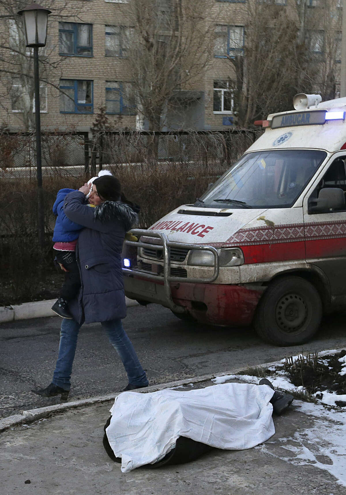 A woman carrying a child walks past the body of a child covered with a cloth after shelling between Russian-backed separatists and Ukrainian government forces in a residential area of the town of Artemivsk, Ukraine, Friday, Feb. 13, 2015. Despite a looming cease-fire deal for eastern Ukraine, a government-held town 40 kilometers (25 miles) behind the front line has been hit by shelling, killing at least one person. The deadline for the warring sides to halt hostilities is Sunday morning at one minute after midnight. (AP Photo/Petr David Josek)