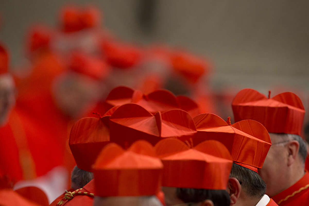 Cardinals wearing their red three-cornered biretta hats gather during a ceremony in St. Peter's Basilica at the Vatican, Saturday, Feb. 14, 2015. Pope Francis welcomed 20 new cardinals Saturday into the elite club of churchmen who will elect his successor and immediately delivered a tough-love message to them, telling them to put aside their pride, jealousy and self-interests and instead exercise perfect charity.Retired Pope Benedict XVI was on hand for the ceremony, sitting off to the side in the front row of the basilica, in a unique blending of popes past, present and future. Francis embraced him at the start and end of the service and a cluster of cardinals lined up to greet him before processing out. (AP Photo/Andrew Medichini)