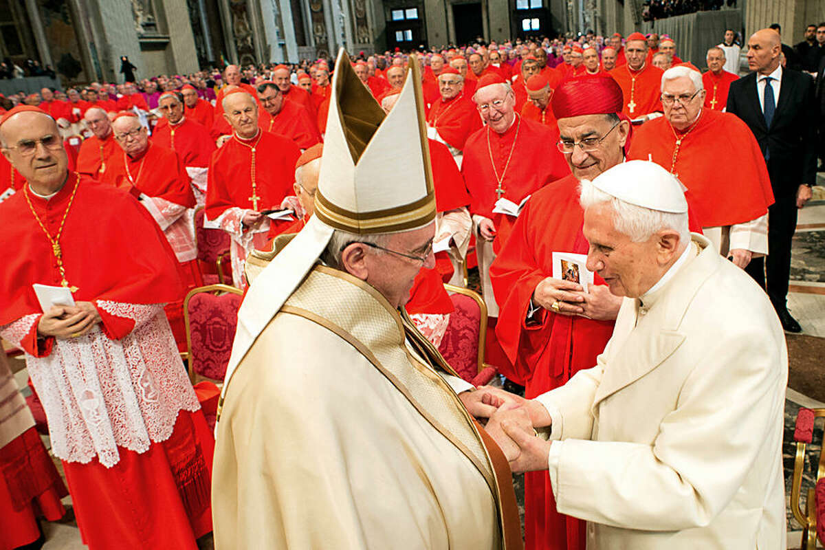 Pope Emeritus Benedict XVI, right, greets Pope Francis in St. Peter's Basilica at the Vatican, Saturday, Feb. 14, 2015. Pope Francis welcomed 20 new cardinals Saturday into the elite club of churchmen who will elect his successor and immediately delivered a tough- love message to them, telling them to put aside their pride, jealousy, self-interests and anger and instead exercise perfect charity. Francis issued the marching orders during the ceremony in St. Peter's Basilica to elevate the new