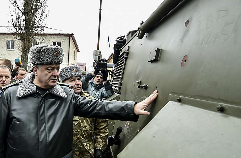 Ukraine's President Petro Poroshenko inspects a British Saxon military vehicle for its bullet proof capabilities at the National Guard Training Center in Novy Petrivtsy, Ukraine, Friday, Feb. 13, 2015. The first twenty Saxons, after equipping them with weapons, will be sent to the Ukrainian east . (AP Photo/ Mykola Lazarenk, Pool)
