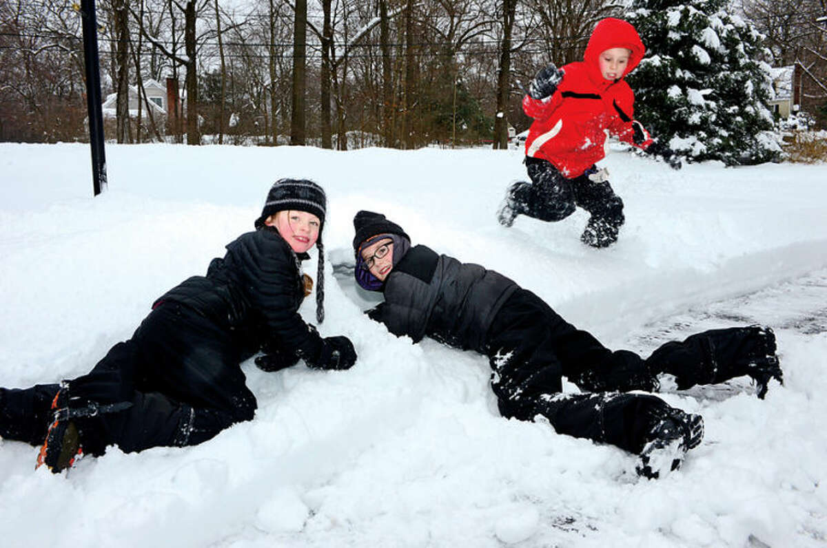 Hour photo / Erik Trautmann Garrett Moe, 9, and his sister Lauren, 7, make a snow fort with their friend Jack Christman, 9, following the recent winter storm that left 5 inches of wet snow in Wilton Wednesday morning.
