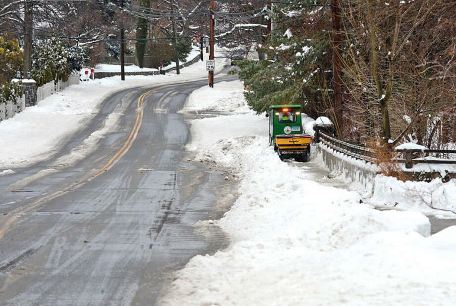 Hour photo / Erik Trautmann The City of Stamford clears the sidewalk on a bridge off Glenbrook Rd. following the recent winter storm that left 5 inches of wet snow Wednesday morning.