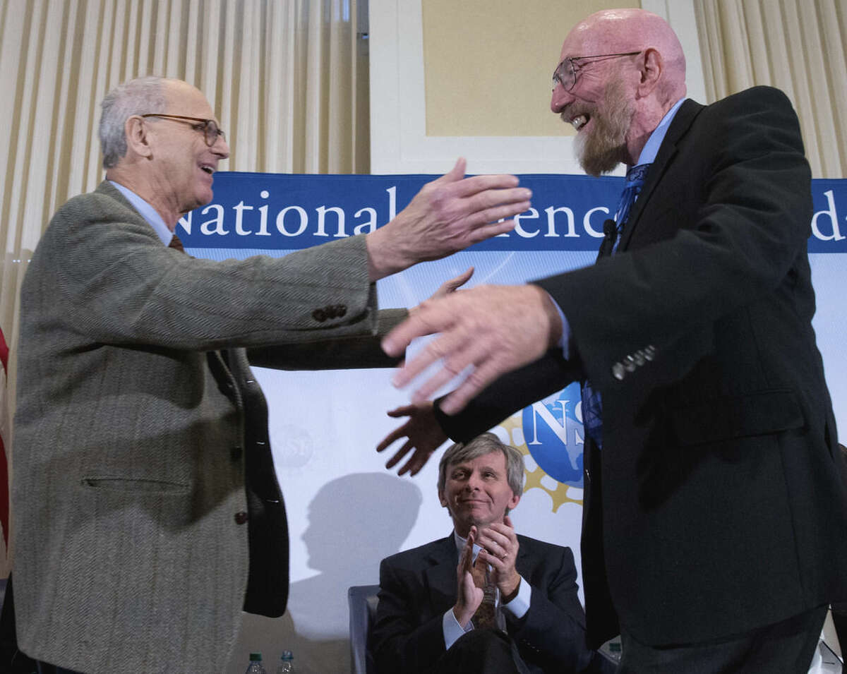 Laser Interferometer Gravitational-Wave Observatory (LIGO) Co-Founder Rainer Weiss, left, and Kip Thorne, right, accompanied by Interferometer Gravitational-Wave Observatory (LIGO) Exectutive Director David Reitze, bottom, hug on stage during a news conference at the National Press Club in Washington, Thursday, Feb. 11, 2016, to announce that scientists have detected gravitational ripples, just as Einstein predicted a century ago. (AP Photo/Andrew Harnik)
