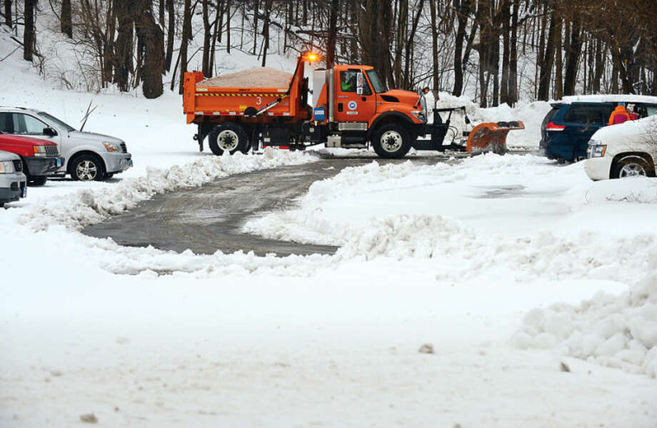 Hour photo / Erik Trautmann CT DPW trucks begins clearing the commuter lots where some vehicles were stranded following the recent winter storm that left 5 inches of wet snow Wednesday morning.