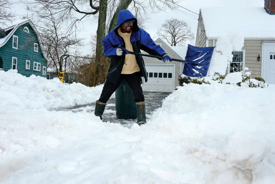 Hour photo / Erik Trautmann Garnett Salkie shivels snow in front of his home on Gregory Blvd following the recent winter storm that left 5 inches of wet snow Wednesday morning.