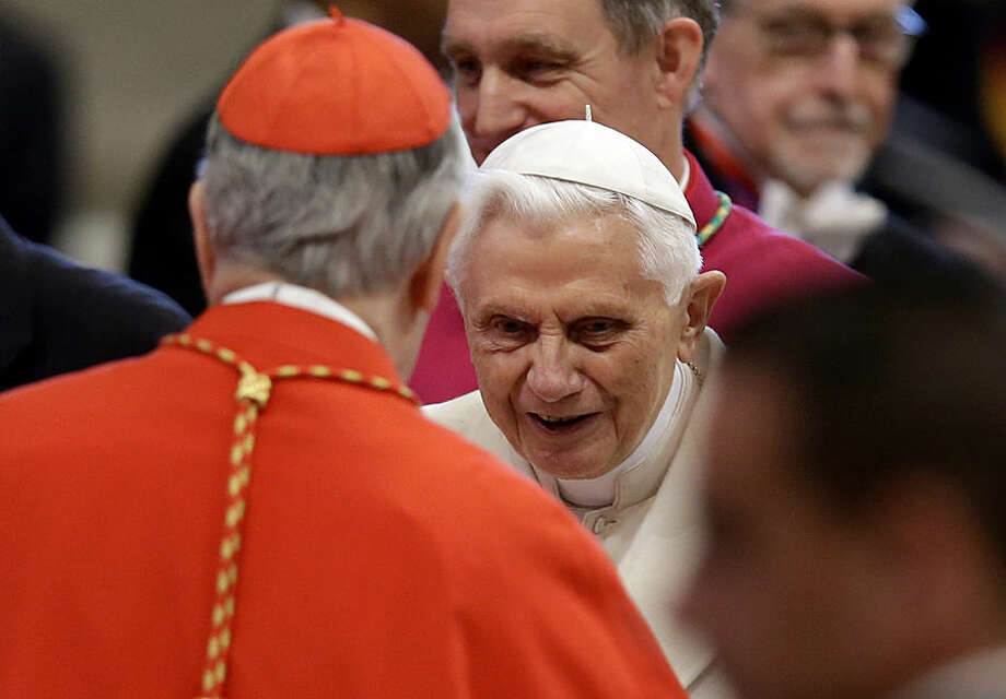 Pope Emeritus Benedict XVI, center, arrives for a ceremony in St. Peter's Basilica at the Vatican, Saturday, Feb. 14, 2015. Pope Francis is expanding the ranks of cardinals who will elect his successor to include pastors like him who minister to the poor and come from far-flung, often overlooked dioceses. Francis was formally elevating the 20 new cardinals at a ceremony Saturday in St. Peter's Basilica. Retired Pope Benedict XVI was expected to be on hand in a unique blending of popes past, present and future. (AP Photo/Andrew Medichini)