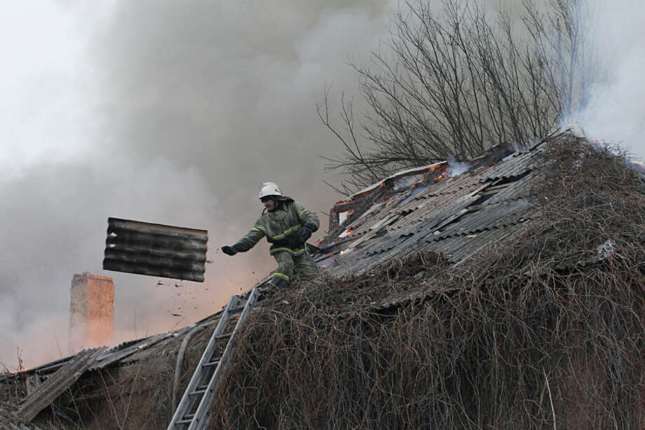 A firefighter dismantles a roof to extinguish a building on fire after shelling between Russian-backed separatists and Ukrainian government in residential area of the town of Artemivsk, Ukraine, Saturday, Feb. 14, 2015. Despite a looming cease-fire deal for eastern Ukraine, a government-held town 40 kilometers (25 miles) behind the front line has been hit by shelling. The deadline for the warring sides to halt hostilities is Sunday morning at one minute after midnight. (AP Photo/Petr David Josek)