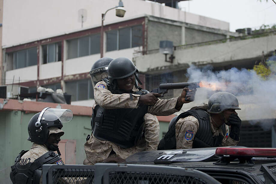 A national police officer fires a tear gas grenade towards protesters demanding that the government lower fuel prices, in Port-au-Prince, Haiti, Friday, Feb. 13, 2015. Students marched through Haiti's capital to demand lower gas prices and the ouster of President Michel Martelly. ( AP Photo/Dieu Nalio Chery)