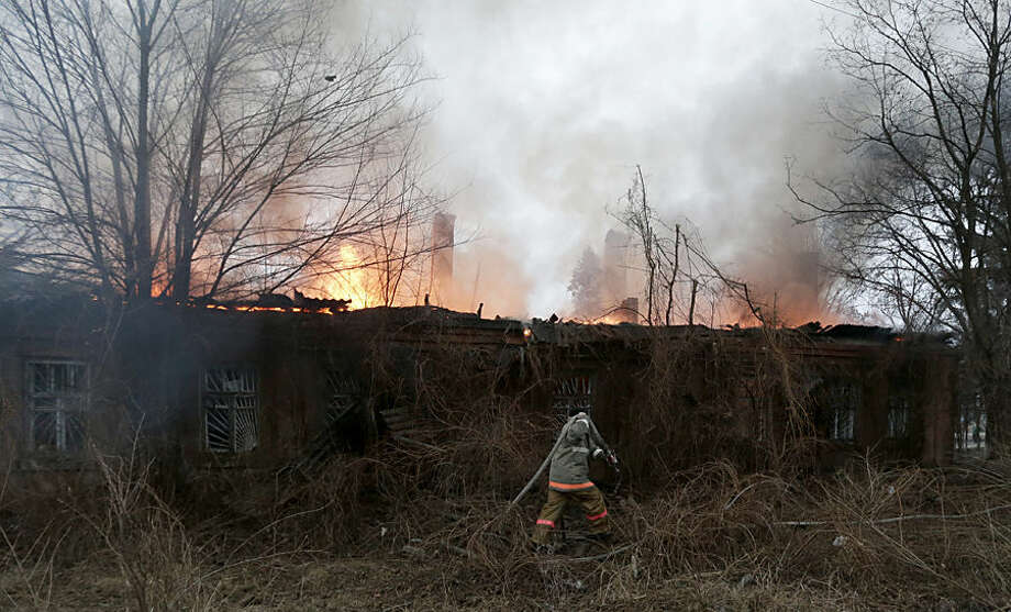 A firefighter carries a hose in an effort to extinguish a building on fire after shelling between Russian-backed separatists and Ukrainian government in residential area of the town of Artemivsk, Ukraine, Saturday, Feb. 14, 2015. Despite a looming cease-fire deal for eastern Ukraine, a government-held town 40 kilometers (25 miles) behind the front line has been hit by shelling. The deadline for the warring sides to halt hostilities is Sunday morning at one minute after midnight. (AP Photo/Petr David Josek)