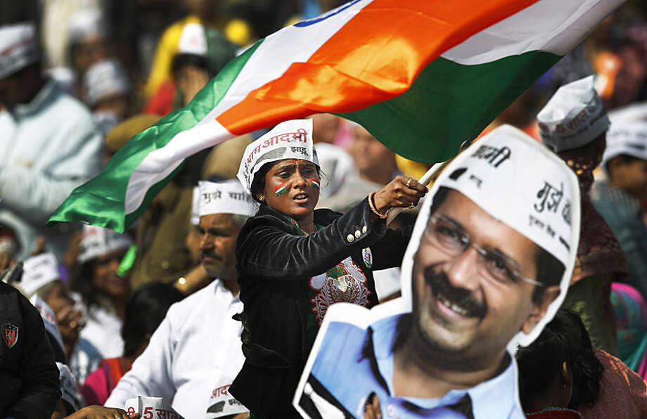 A supporter of Aam Aadmi Party, or Common Man's Party, waves an Indian flag next to a cut-out of party leader Arvind Kejriwal during his swearing-in ceremony as chief minister of Delhi in New Delhi, India, Saturday, Feb. 14, 2015. The AAP, headed by the former tax official who had remade himself into a champion for clean government, won 67 of the 70 seats in recent elections. (AP Photo/Altaf Qadri)
