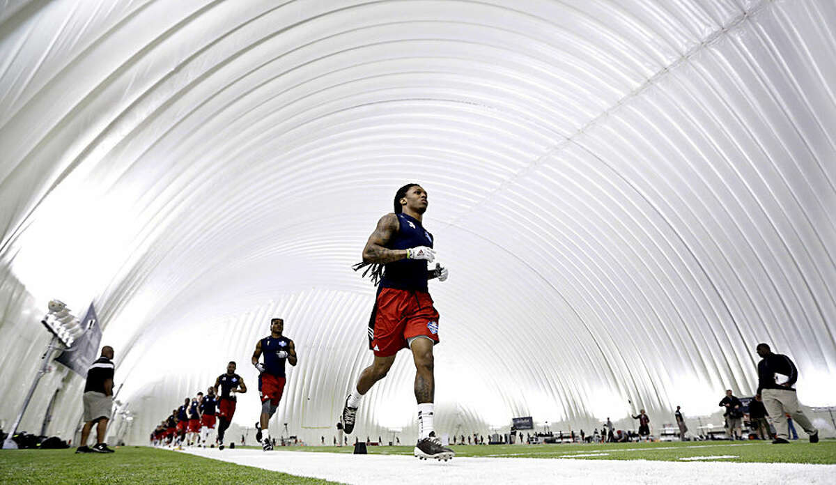 Floyd Raven, of Texas A&M, runs with other draft-eligible players at the NFL football regional combine Saturday, Feb. 14, 2015, at the Houston Texans' training facility in Houston. Players that do well at the regional combine will be invited to attend the NFL super regional combine. (AP Photo/David J. Phillip)