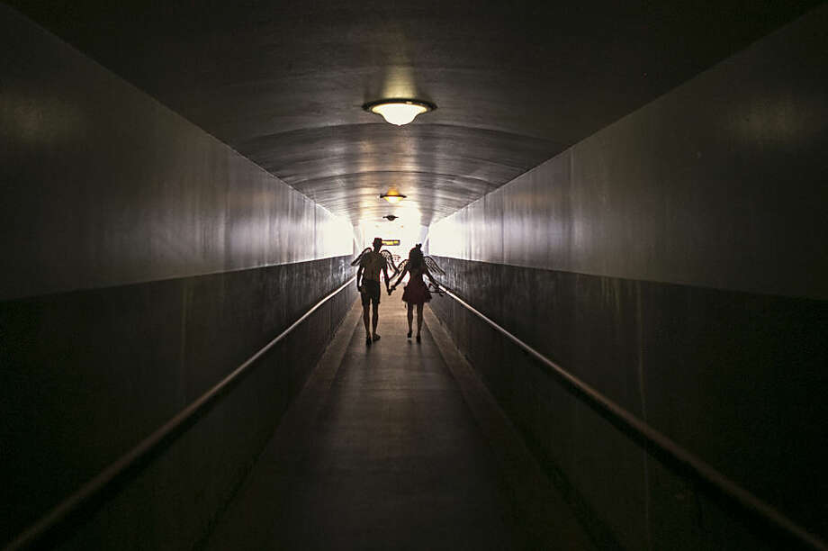 """Performers Shauna Hackney, right, and Jared Hansen, dressed as """"Metro Cupids,"""" walk into a tunnel at Union Station in Los Angeles, Friday, Feb. 13, 2015. Los Angeles Metro celebrates Valentine's Day a day early with its second annual """"Speed Dating on the Red Line"""" event, helping passengers seeking to celebrate love while in transit. (AP Photo/Damian Dovarganes)"""