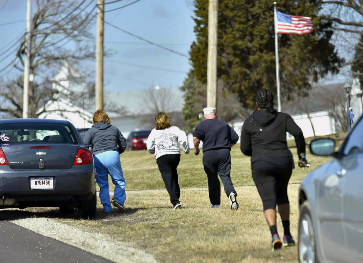 Parents run to see if they are allowed to pick up their kids at Madison Local Schools, Monday, Feb. 29, 2016, in Madison Township in Butler County, Ohio, after a school shooting. An Ohio sheriff says a 14-year-old suspect in the school shooting that wounded multiple classmates is in custody. (Nick Graham/Dayton Daily News via AP)