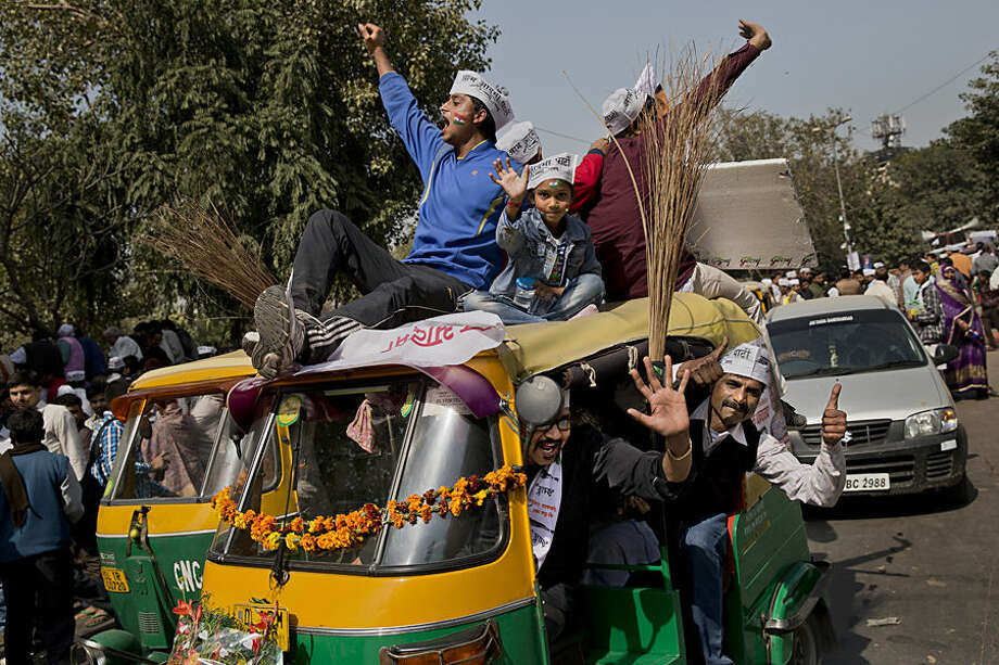 Supporters of the Aam Aadmi Party, or Common Man's Party, shout slogans as they sit on an autorickshaw decorated with brooms, the party symbol, outside the venue where party leader Arvind Kejriwal is being sworn-in as the new chief minister of Delhi, in New Delhi, India, Saturday, Feb. 14, 2015. Kejriwal and the party he created routed the country's best-funded and best-organized political machine and dealt an embarrassing blow to Prime Minister Narendra Modi. (AP Photo/Bernat Armangue)