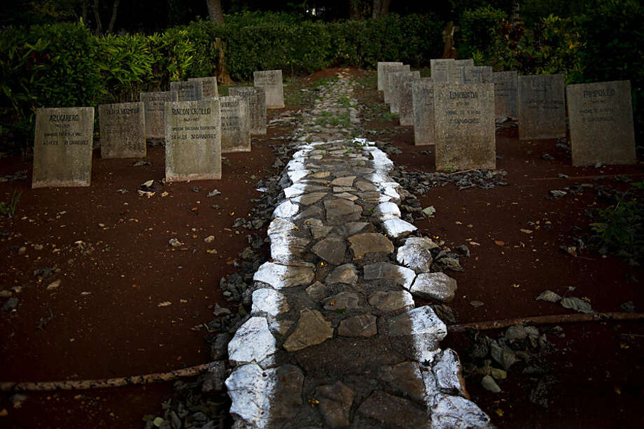 In this Feb. 4, 2015 photo, tombstones of the first stallions at the state-run Azucarero horse ranch, where an artificial insemination program is being developed, stand in a horse cemetery at the ranch in Artemisa, Cuba. The tombstones carry the horses' names, birthdays, the years they died, their number of offspring as well as how many of their offspring were winners. Some of the names on the tombstones are Azucarero, Rincon Criollo, Playa Hermosa, Discutido, Limonada and Pimpollo. (AP Photo/Ramon Espinosa)