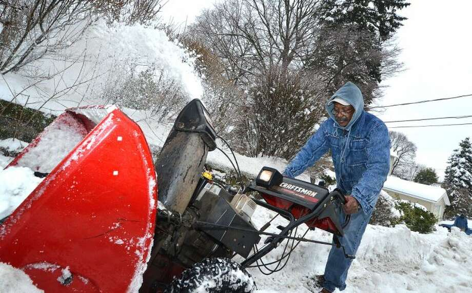 Hour Photo/Alex von Kleydorff. John Ruffin pushes his snowblower trough the heavy snow to clear the sidewalk for pedetstrians in front of his Norwalk home on Wednesday