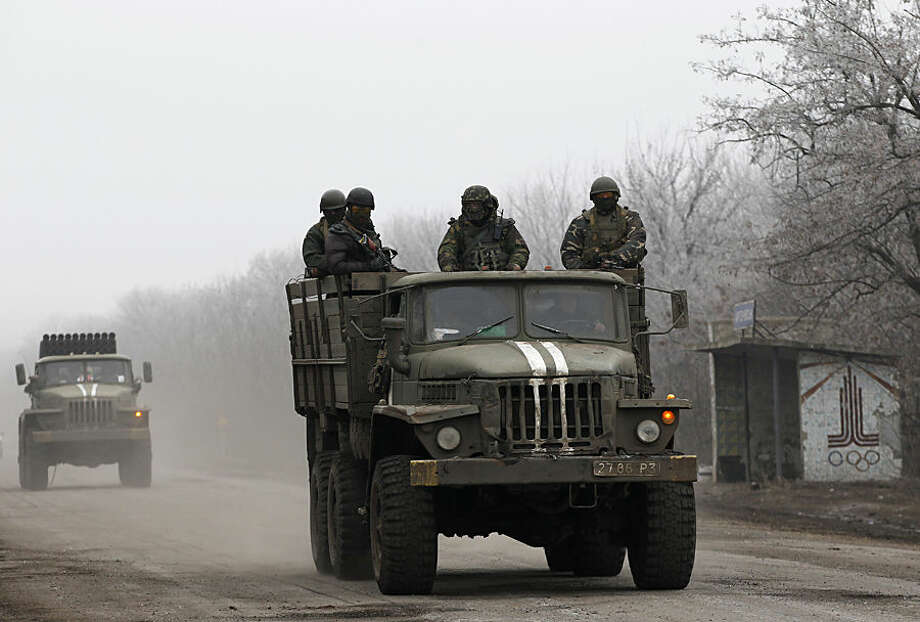 Ukrainian government soldiers ride on a vehicle on the road between the towns of Dabeltseve and Artemivsk, Ukraine, Saturday, Feb. 14, 2015. The fighting between Russia-backed separatists and Ukrainian government forces has continued despite the agreement reached by leaders of Russia, Ukraine, Germany and France in the Belarusian capital of Minsk on Thursday. Much of the fighting had taken place near Debaltseve, a key transport hub that has been hotly contested in recent days. The leaders agreed to implement a cease-fire, set to take effect on Sunday, at one minute after midnight. (AP Photo/Petr David Josek)