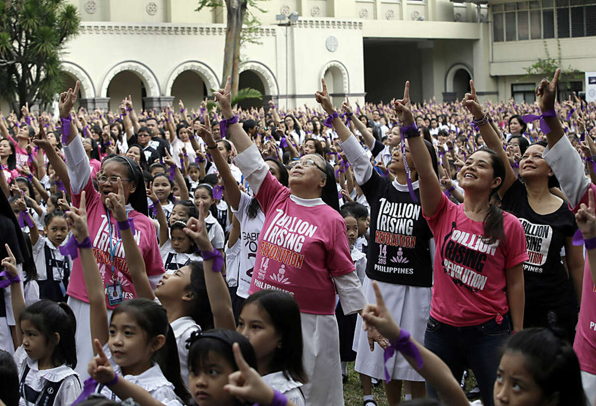 With purple ribbons on their wrists, more than 3,000 students, teachers and nuns from the Catholic-run St. Scholastica's College in Manila, flash the No.1 sign as they dance at their quadrangle to take part in the global campaign to end violence against women and girls dubbed One Billion Rising, Friday, Feb. 13, 2015 in Manila, Philippines. (AP Photo/Bullit Marquez)