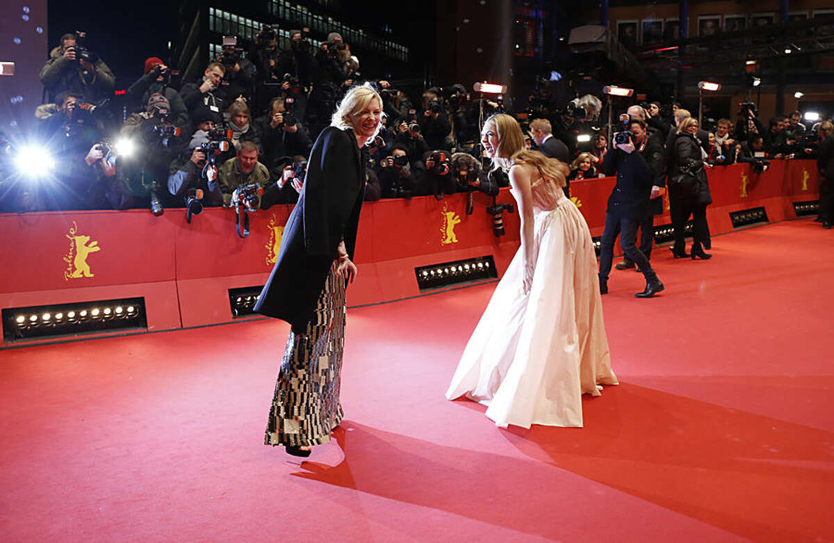 Actresses Cate Blanchett and Lily James share a joke on the red carpet for the film Cinderella at the 2015 Berlinale Film Festival in Berlin, Germany, Friday, Feb. 13, 2015. (AP Photo/Markus Schreiber)