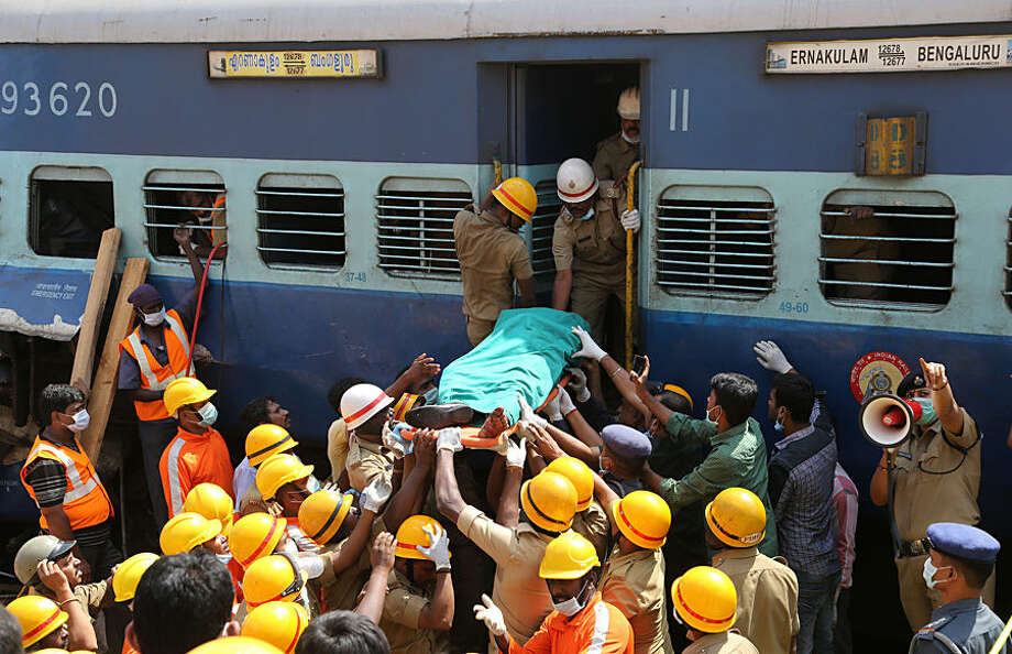 Rescuers carry body of a victim of a train that derailed near Anekal, about 40 kilometers south of Bangalore, India, Friday, Feb. 13, 2015. A train derailed after hitting a boulder that had fallen on the track in southern India on Friday, killing more than 10 people and injuring dozens, officials said. (AP Photo/Aijaz Rahi)